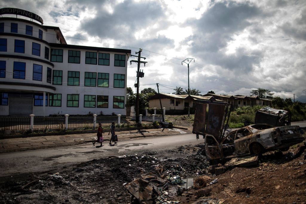 Women pass by the edge of the abandoned market into the majority anglophone South West province in Buea, on October 3, 2018 next the wreckage of a car burned allegedly by separatists fighter in a recent attack. - The southwest, along with the northwest, has been torn by two-years of clashes between English-speaking fighters, who want to break away from majority francophone Cameroon, and government forces.