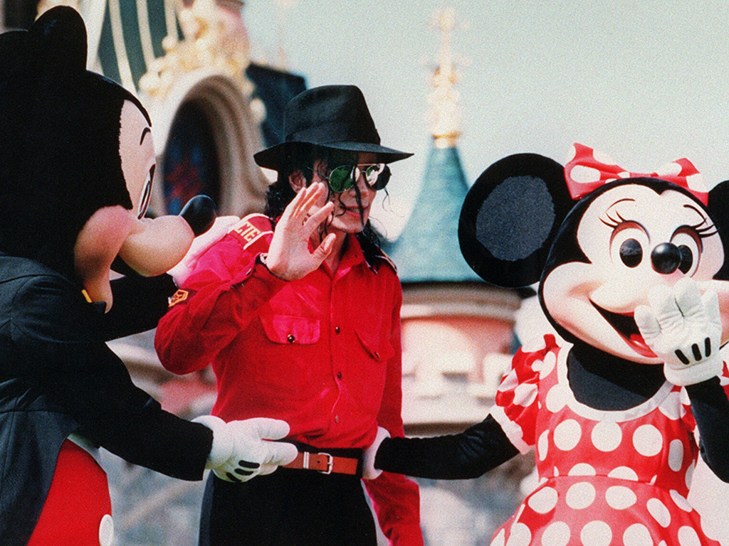 Michael Jackson, flanked by Mickey Mouse and Minnie, waves to fans July 27, 1992 during his suprise visit to the EuroDisney.
