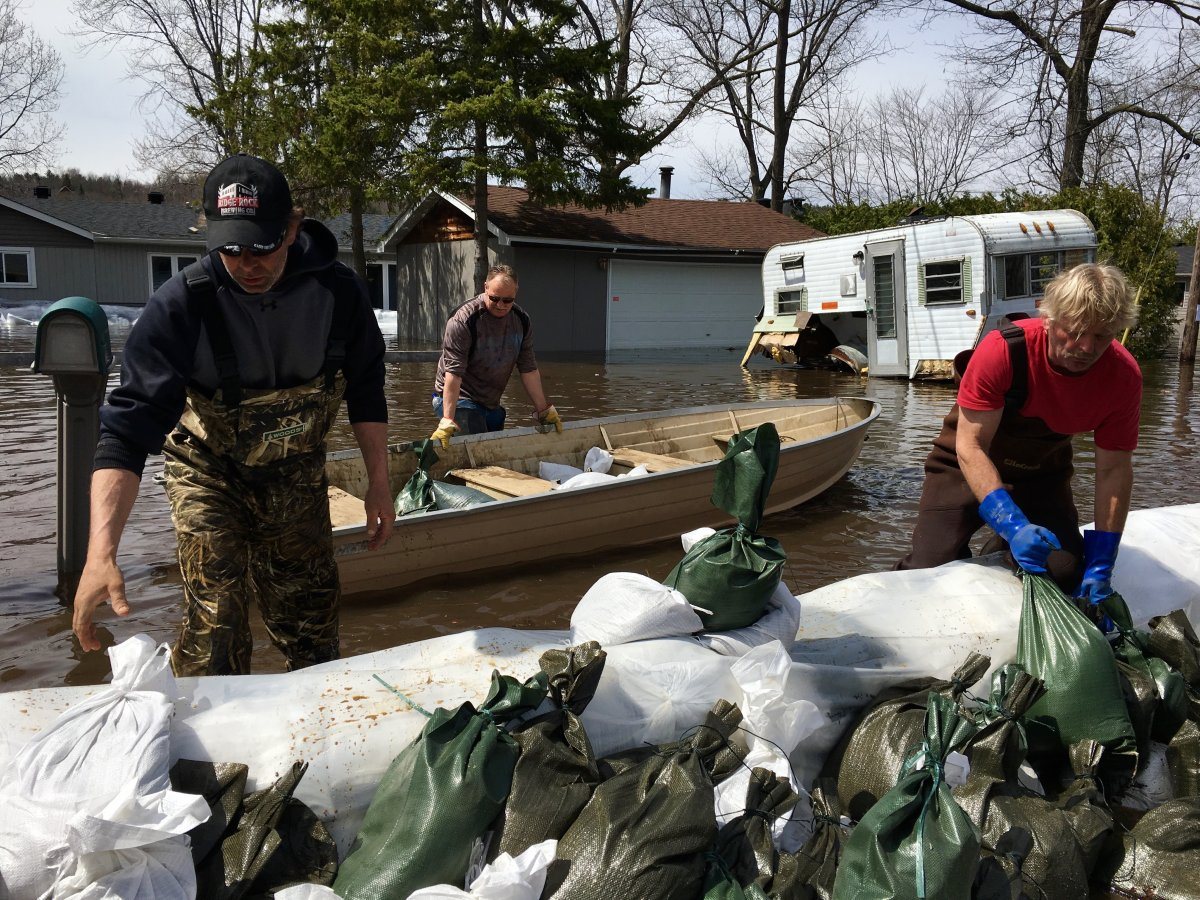 Homeowners and volunteers transport sandbags in boats to homes surrounded by water on Bayview Drive in Constance Bay on Monday, April 29, 2019.