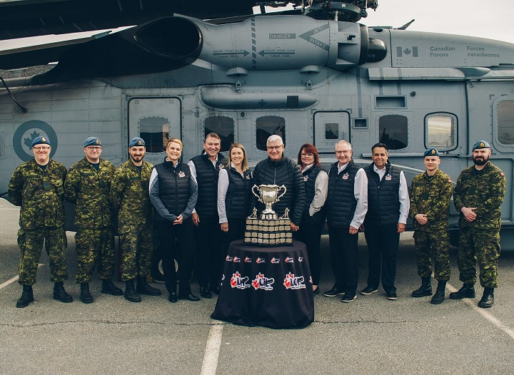 Surrounded by members of the military, members of the 2020 host committee from Kelowna stand behind the Memorial Cup. From left: Renta Mills, Tom Dyas, Jillian Wegner, Bruce Hamilton, Anne-Marie Hamilton, Gavin Hamilton and Thom Killingsworth.