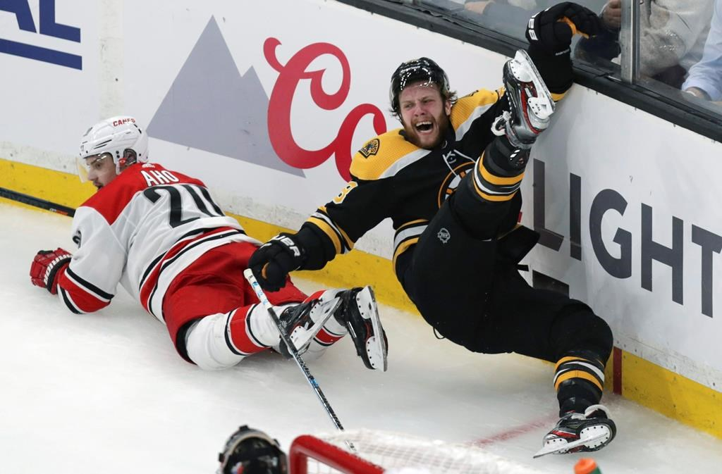 Boston Bruins' David Pastrnak, right, is upended after a check by Carolina Hurricanes' Sebastian Aho (20), of Finland, during the third period in Game 1 of the NHL hockey Stanley Cup Eastern Conference finals Thursday, May 9, 2019, in Boston. (AP Photo/Charles Krupa).