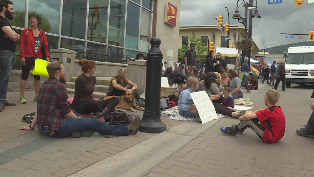 Dozens of people showed up to a protest on May 25 to voice opposition to Penticton's proposed bylaw change that would ban sitting or lying on sidewalks during the summer months.