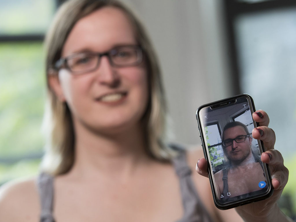 Bailey Coffman shows her photo as a man in the Snapchat app during an interview in New York. Snapchat's new photo filter allows users to change into a man or woman with the tap of a finger.