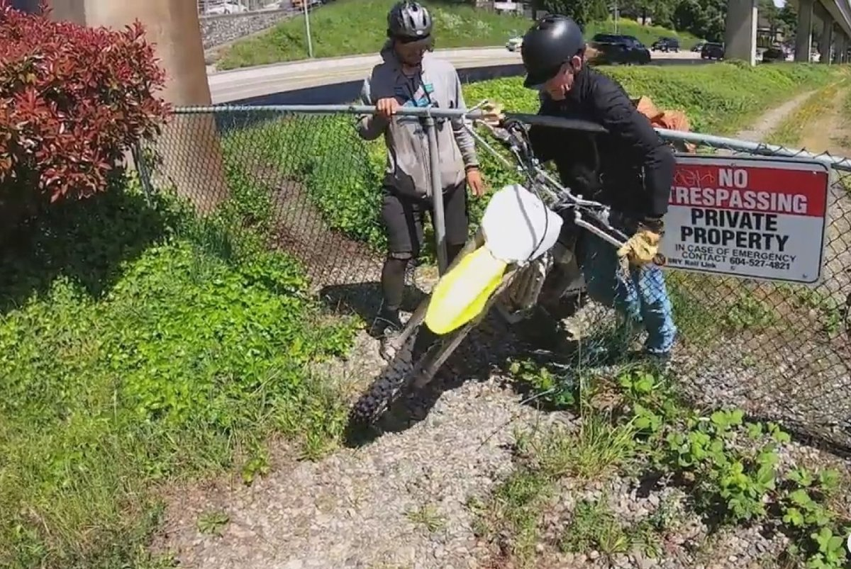 Two men are confronted while pushing a dirt bike through a chainlink fence on the side of Stewardson Way in New Westminster. The bike turned out to belong to the friend of the man taking the video.