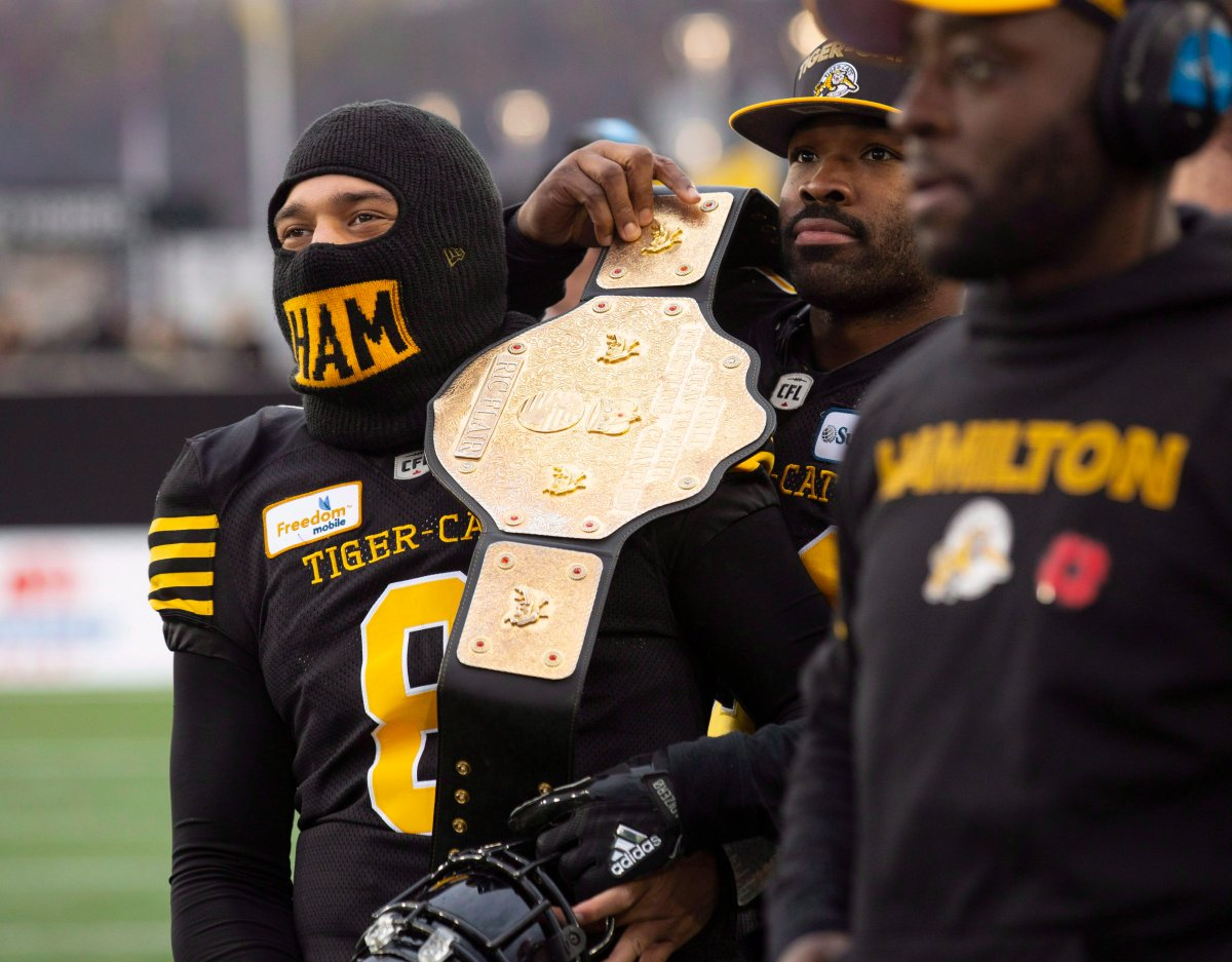 Hamilton Tiger-Cats linebacker Simoni Lawrence (21) puts a wrestling belt over the shoulder of quarterback Jeremiah Masoli (8) during second half CFL Football division semifinal game action against the B.C. Lions in Hamilton, Ont., on Nov. 11, 2018.