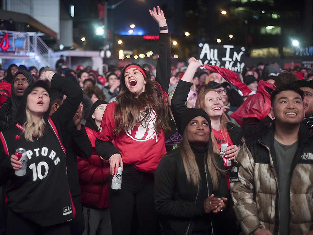 In this May 12, 2019, photo, basketball fans cheer for the Toronto Raptors before claiming victory over the Philadelphia 76ers outside Maple Leaf Square in Toronto.