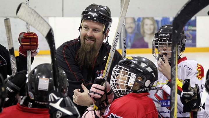Hockey Education Reaching Out Society (HEROS) program manager Kevin Hodgson, centre, works with disadvantaged kids during an on-ice session in Calgary, Alta., Dec. 20, 2012.