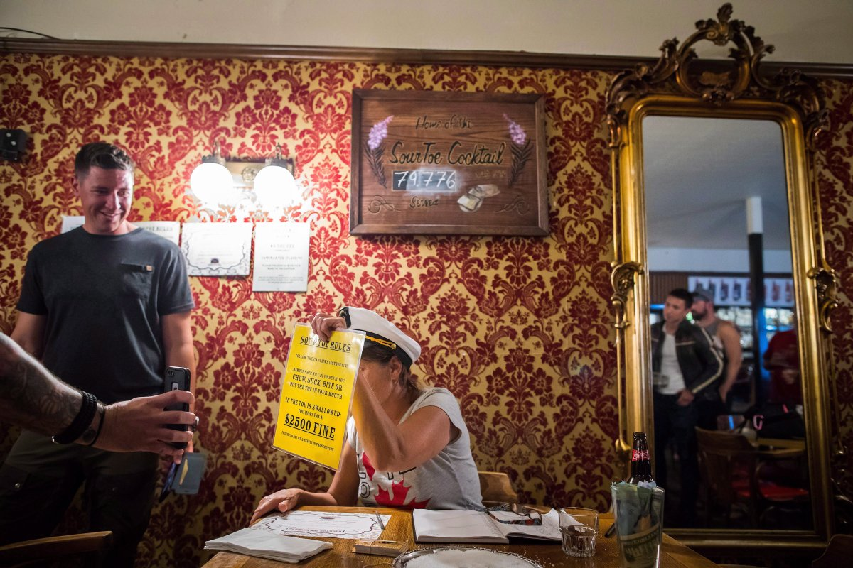 """""""Toe Captain"""" Sue Taylor holds up a list of rules while administering the drinking of the Sourtoe Cocktail, a drink containing a dehydrated human toe, in Dawson City, Yukon, on Sunday, July 1, 2018."""