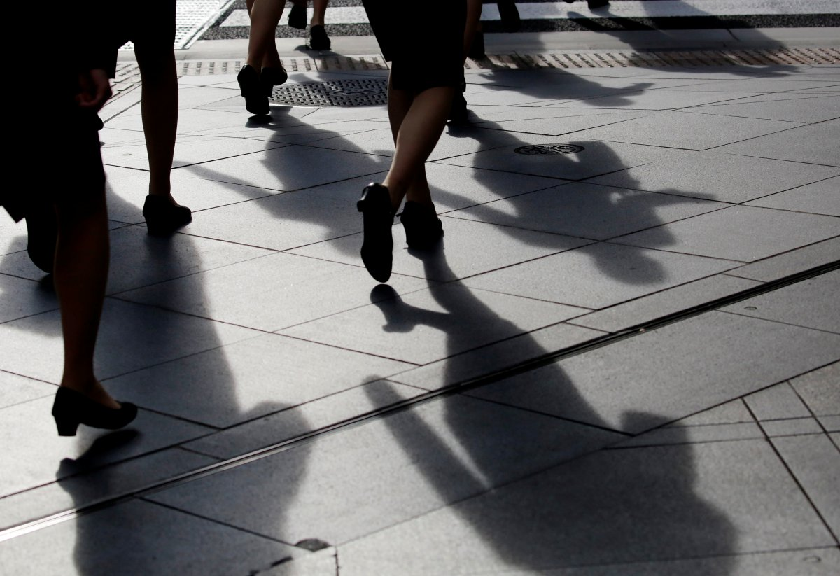 Female office workers wearing high heels and clothes of the same colour walk at a business district in Tokyo, Japan, June 4, 2019.