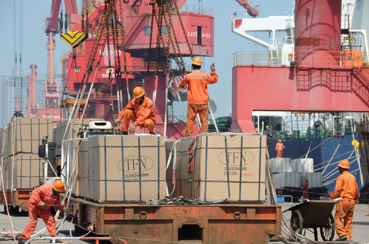 Workers load goods for export onto a crane at a port in Lianyungang .