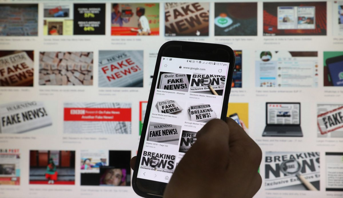 A person scrolls the screen of a mobile phone while loading information on how to counter fake news in New Delhi, India, in May 2019.