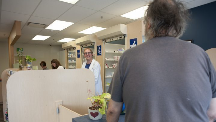 Matthew Manz, left, helps a customer at the pharmacy he manages in Regina, Sask., on  May 31, 2019.