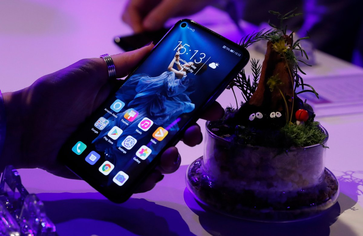 FILE - In this Tuesday, May 21, 2019 file photo, a member of the media tries out new Huawei Honor 20 series of phones following their global launch in London.