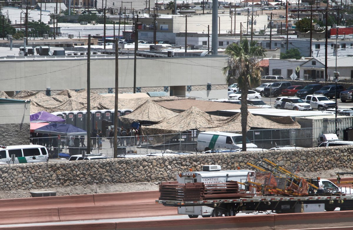 In this June 12, 2019 ,photo, migrants are seen within a fenced-off area inside a temporary outdoor encampment where they're waiting to be processed in El Paso, Texas.