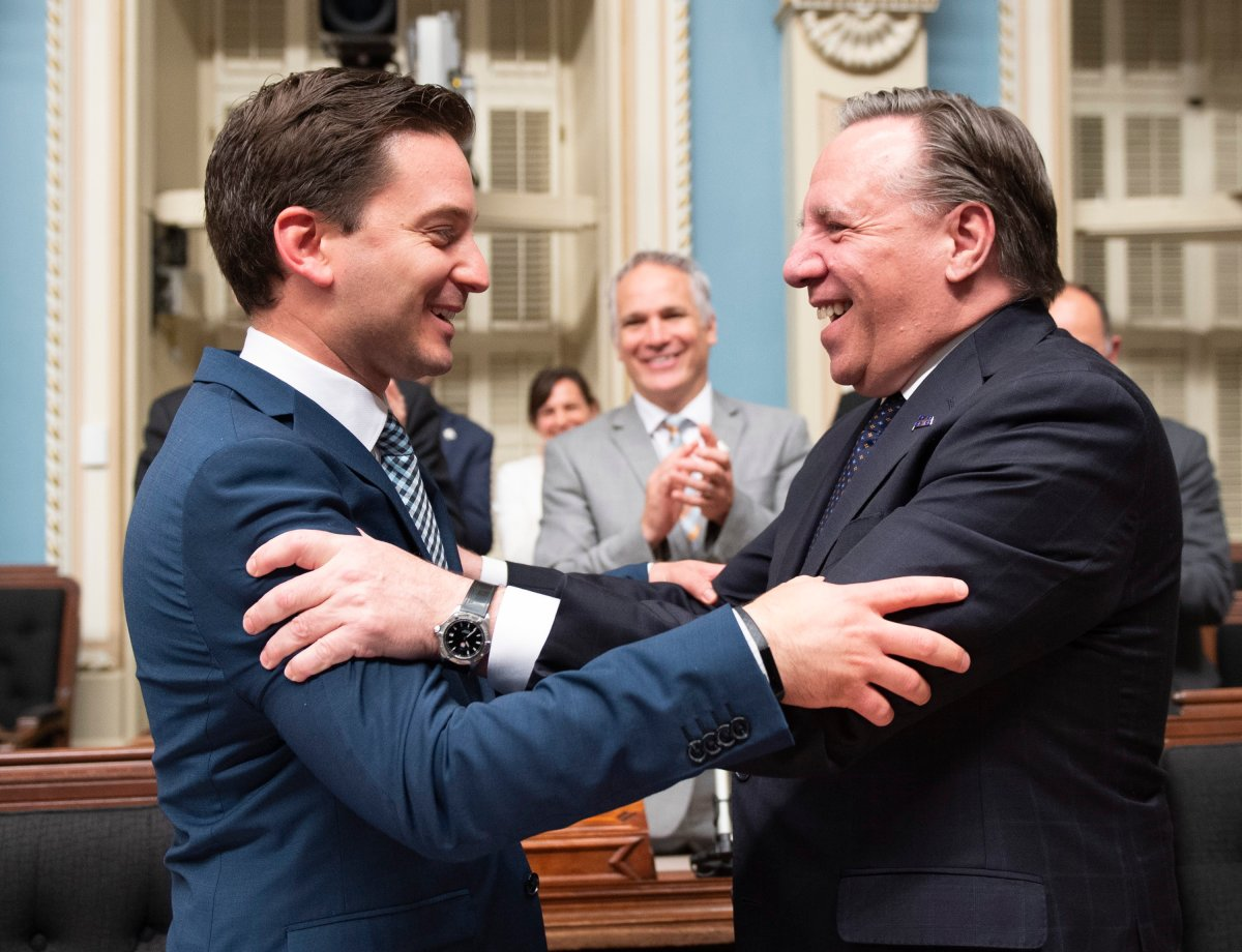 Quebec Minister of Immigration, Diversity and Inclusiveness Simon Jolin Barrette, left, is congratulated by Quebec Premier Francois Legault after they voted a legislation on secularism, at the National Assembly in Quebec City, Sunday, June 16, 2019.