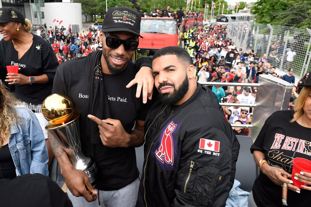 Toronto Raptors forward Kawhi Leonard points at his playoffs MVP trophy as he poses with performing artist Drake during the 2019 Toronto Raptors Championship parade in Toronto on Monday, June 17, 2019.