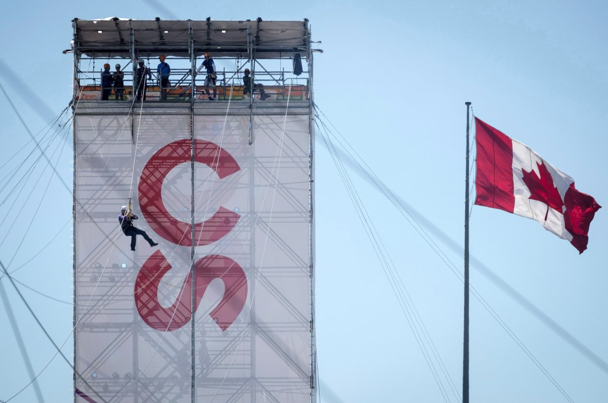 A visitor slides down a zip line during the Calgary Stampede in Calgary, Sunday, July 8, 2018.