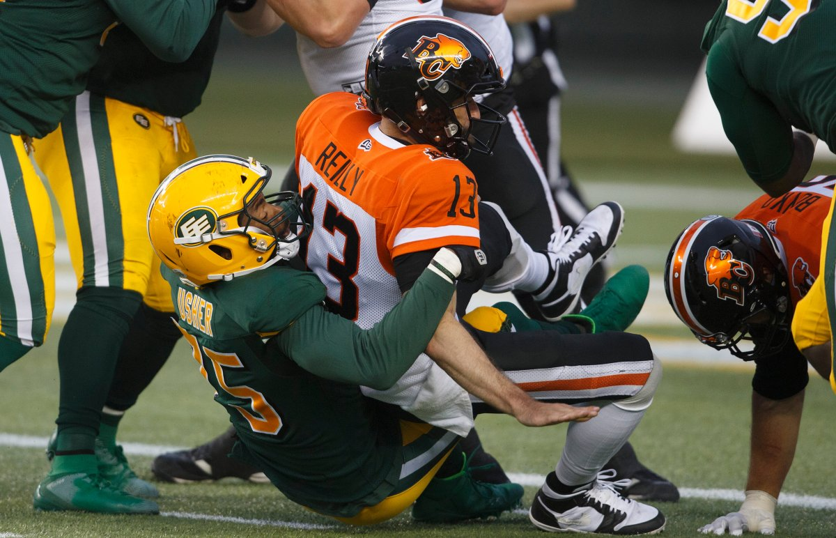 B.C. Lions quarterback Mike Reilly (13) is sacked by Edmonton Eskimos Nick Usher (75) during second half CFL action in Edmonton, Alta., on Friday June 21, 2019.