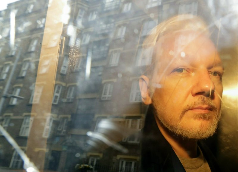 FILE - In this Wednesday, May 1, 2019 file photo, buildings are reflected in the window as WikiLeaks founder Julian Assange is taken from court, where he appeared on charges of jumping British bail seven years ago, in London.