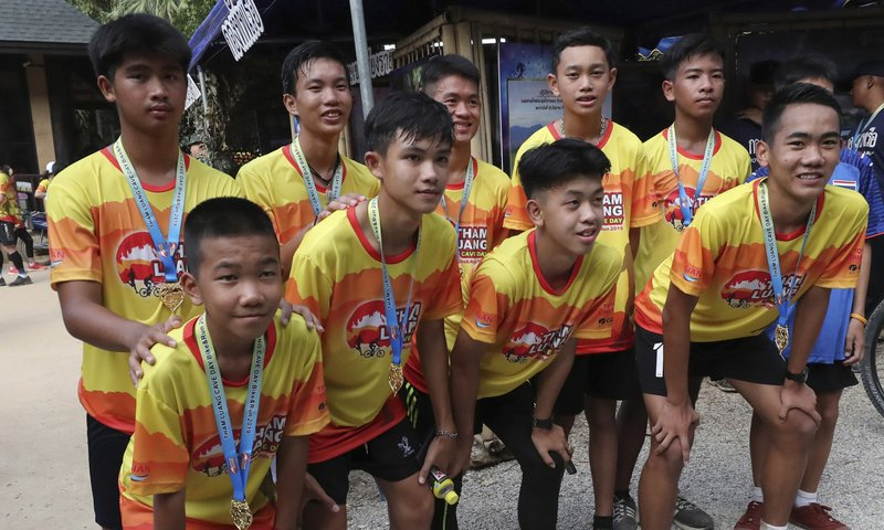 Members of the Wild Boars soccer team who were rescued from a flooded cave, pose for the media after a marathon and biking event in Mae Sai, Chiang Rai province, Thailand, Sunday, June 23, 2019.