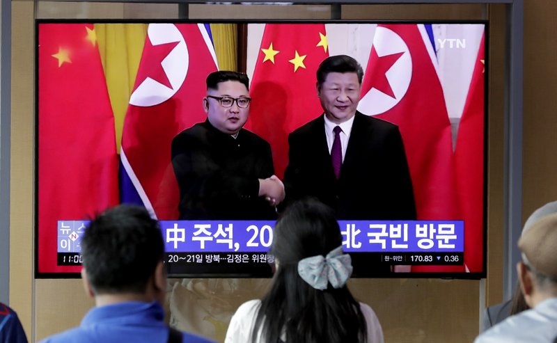 In this June 18, 2019 photo, people watch a TV news program reporting about Chinese President Xi Jinping's state visit to North Korea with a file footage of Chinese President Xi Jinping and North Korean leader Kim Jong Un, at the Seoul Railway Station in Seoul, South Korea. From nukes to huge food aid shipments to a shared skepticism about the United States, Xi and Kim will have a long list of topics to discuss when Xi heads north Thursday, June 20.