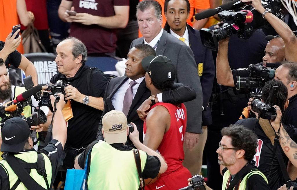 This Thursday, June 13, 2019, photo shows Toronto Raptors general manager Masai Ujiri, center left, walking with guard Kyle Lowry after the Raptors defeated the Golden State Warriors in Game 6 of basketball's NBA Finals in Oakland, Calif.