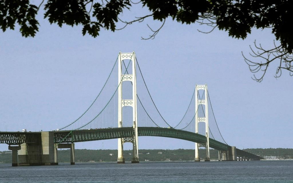 FILE - This July 19, 2002, file photo, shows the Mackinac Bridge that spans the Straits of Mackinac from Mackinaw City, Mich. Enbridge Inc. said Monday, June, 17, 2019, it's moving ahead with collection of rock and soil samples in the Straits of Mackinac while preparing for a court battle with Michigan's governor over a planned oil pipeline tunnel there. The Canadian company, which has been drilling into the ground on the south side of the channel linking Lakes Huron and Michigan, said it will begin boring into the lakebed this week from a barge in shallow water.