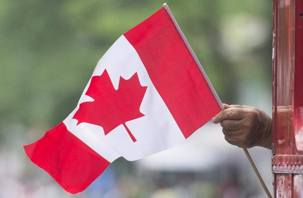 A man waves a flag during a Canada Day parade in Montreal on July 1, 2018.