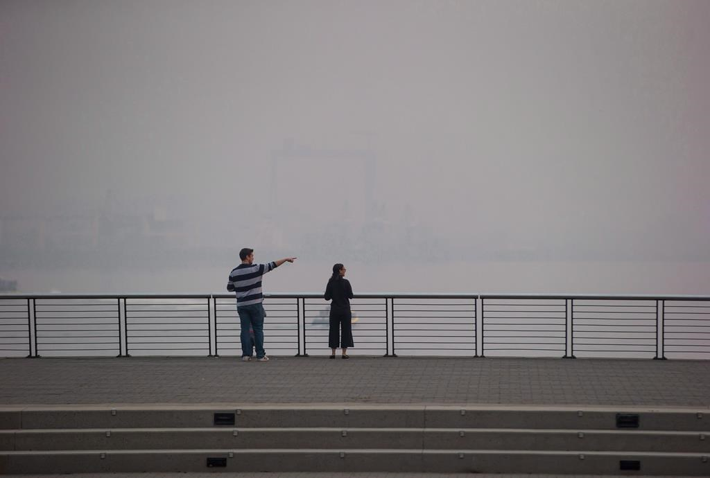 A man and woman look out at the harbour as smoke from wildfires burning in the province fills the air, in Vancouver on August 20, 2018.