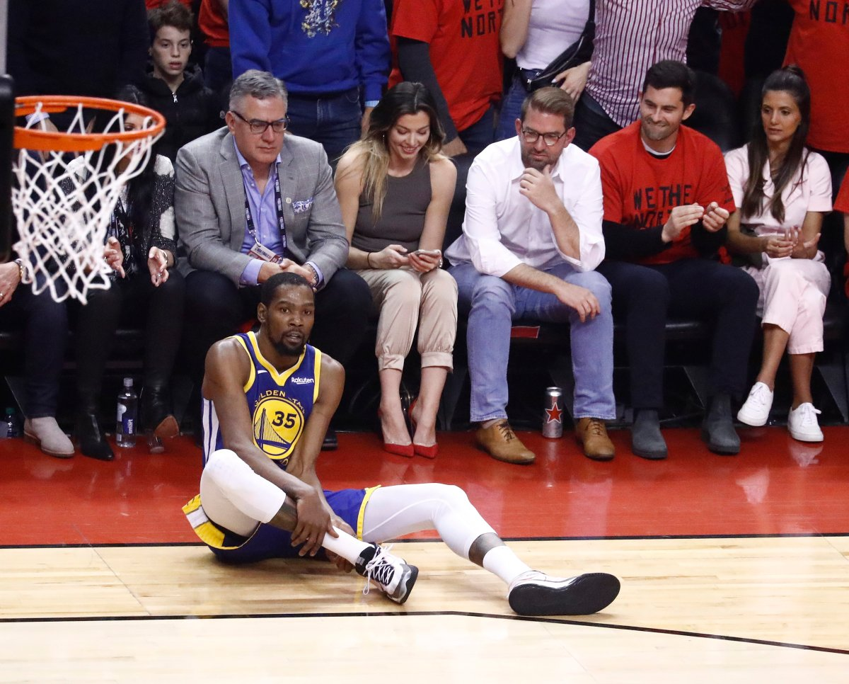 Golden State Warriors forward Kevin Durant holds on to his calf after injuring it in a play against Toronto Raptors center Serge Ibaka during Game 5 of the NBA Finals at Scotiabank Arena in Toronto, Canada, 10 June 2019.