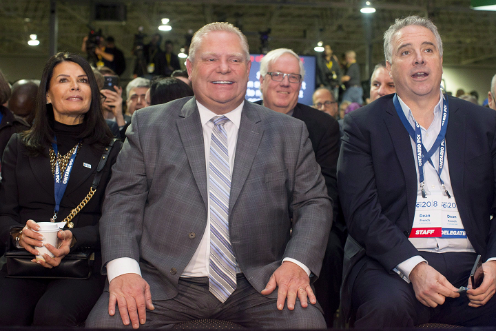 Ontario Premier Doug Ford, centre, sits alongside his wife Karla and Chief of Staff Dean French as they prepare to hear Federal Conservative Leader Andrew Scheer speak at the Ontario PC Convention in Toronto on Saturday, November 17, 2018.
