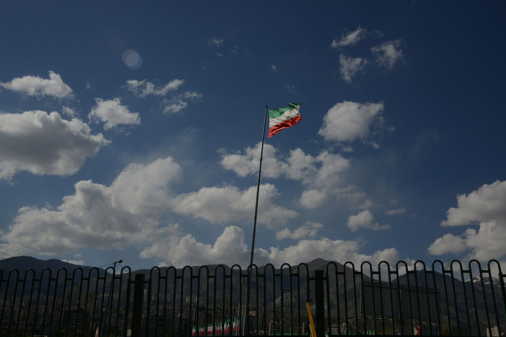 An Iranian flag seen amass against the cloudy blue sky on April 22, 2013 in Tehran, Iran.
