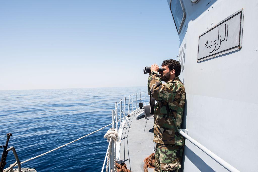 A Libyan coastguard uses binoculars as he patrols the area at sea between Sabratha and Zawiyah on July 28, 2017.
