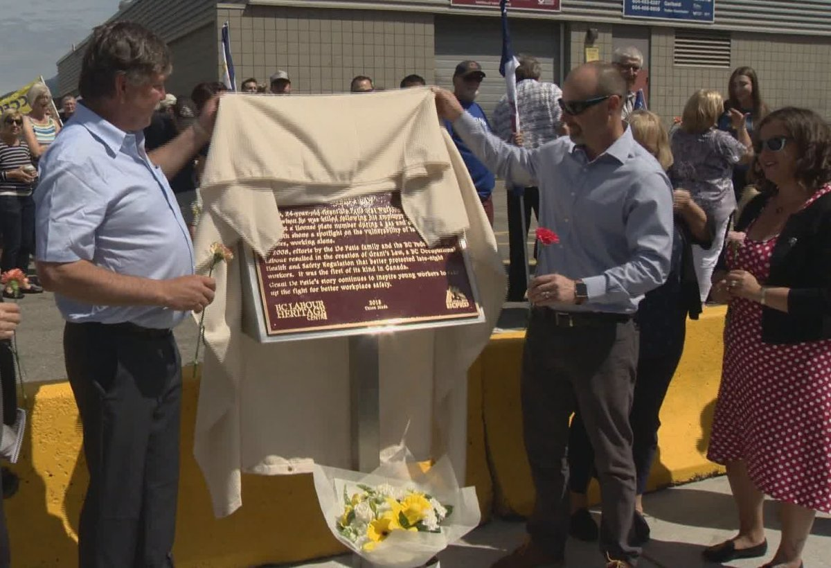 Doug De Patie, left, helps unveil a plaque dedicated to his son Grant outside Garibaldi Secondary School in Maple Ridge on Saturday, June 1, 2019. Grant was killed in March 2005 during an incident at the gas station he worked at that prompted new protections for late-night workers.