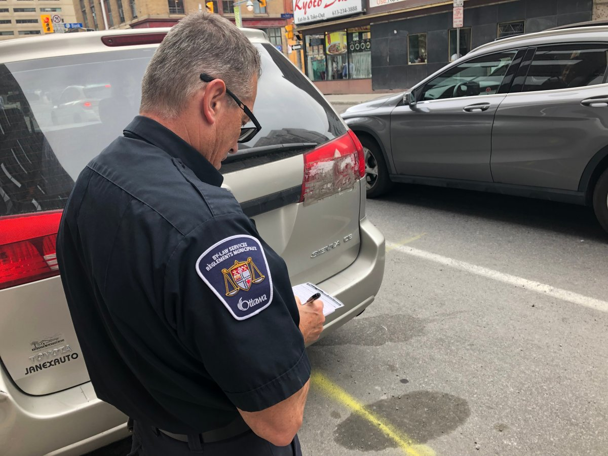 """Parking control officer Danis Lafrance issues a ticket to a vehicle parked in a """"no-stopping zone"""" during Monday's afternoon rush-hour period in downtown Ottawa. The City of Ottawa has got extra bylaw and police officers monitoring streets and intersections for the next two weeks in an effort to ease gridlock on busy roads."""