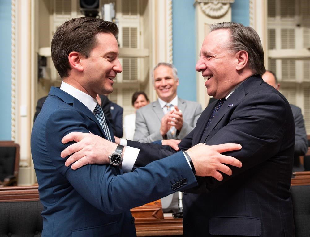 Quebec Minister of Immigration, Diversity and Inclusiveness Simon Jolin Barrette, left, is congratulated by Quebec Premier Francois Legault.