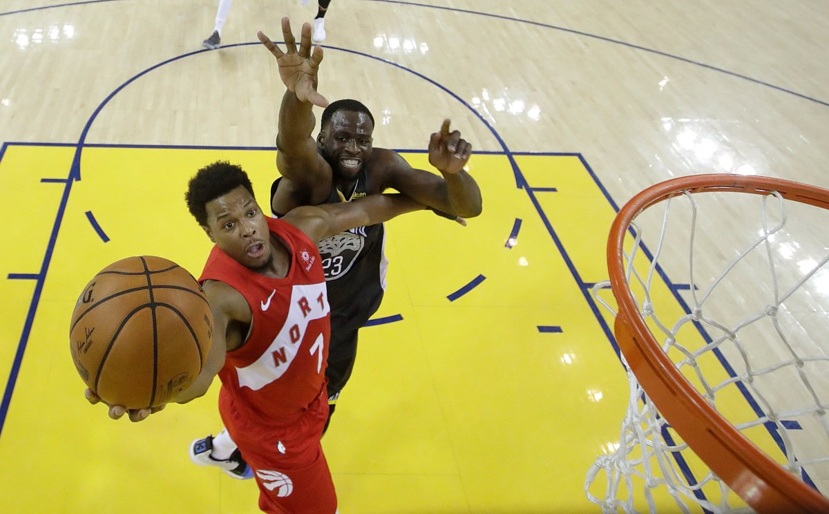 Toronto Raptors guard Kyle Lowry (7) shoots in front of Golden State Warriors forward Draymond Green during the second half of Game 4 of basketball's NBA Finals in Oakland, Calif., Friday, June 7, 2019.
