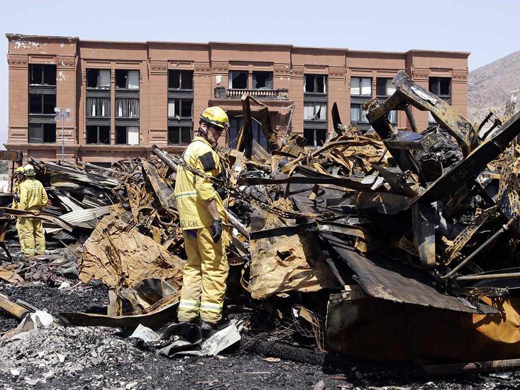 In this June 2, 2008 file photo, Los Angeles County firefighter Darrick Woolever examines metal that needs to be removed at the Universal Studios Hollywood back lot, a day after a fire destroyed the New York Street facade, in the Universal City section of Los Angeles.