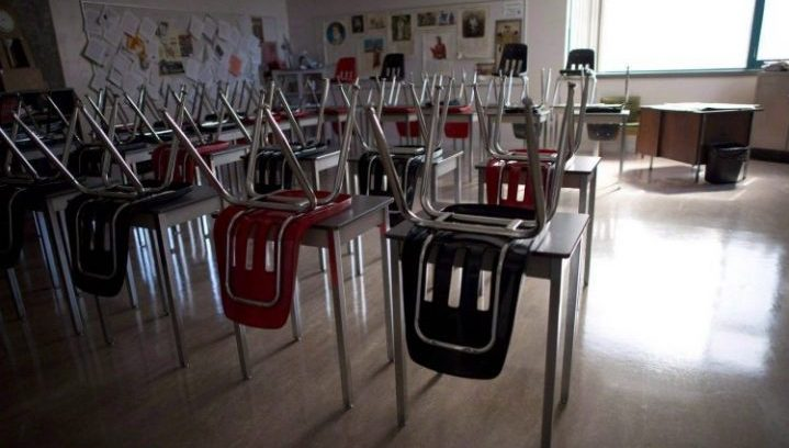 Vacant desks are pictured at the front of an empty classroom.