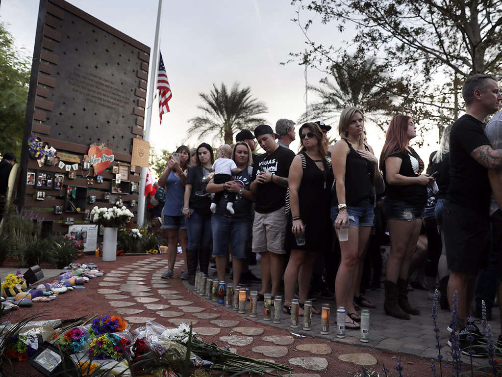 People gather to dedicate a healing garden on the first anniversary of the Oct. 1, 2017 shooting that killed 58 people and wounded hundreds, in Las Vegas, Nev.