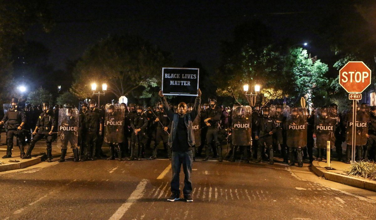 A Black Lives Matter protester stands in front of St. Louis Police Department officers equipped with riot gear after the not guilty verdict in the murder trial of Jason Stockley, a former St. Louis police officer, charged with the 2011 shooting of  Anthony Lamar Smith, who was black, in St. Louis, Missouri, U.S., September 15, 2017.