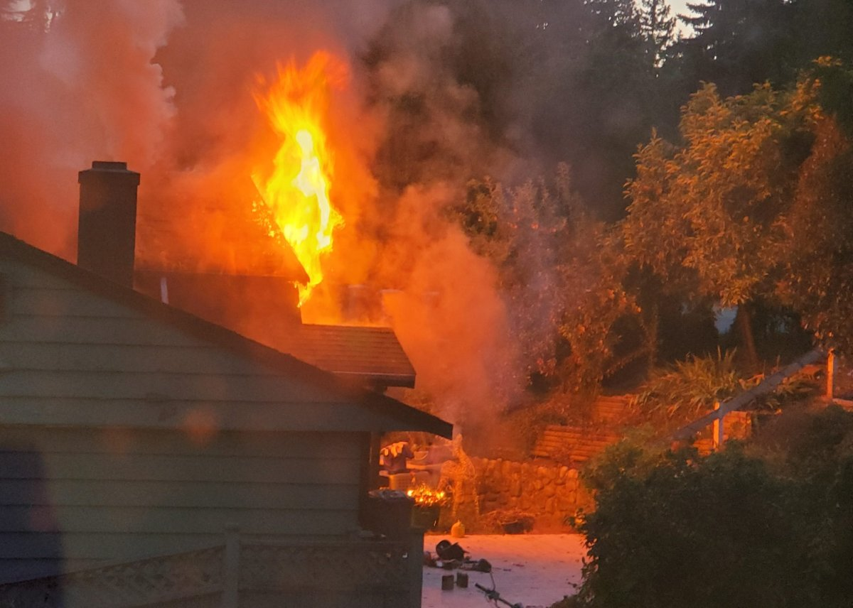Flames shoot out of a home in Burnaby on Saturday, July 20, 2019.