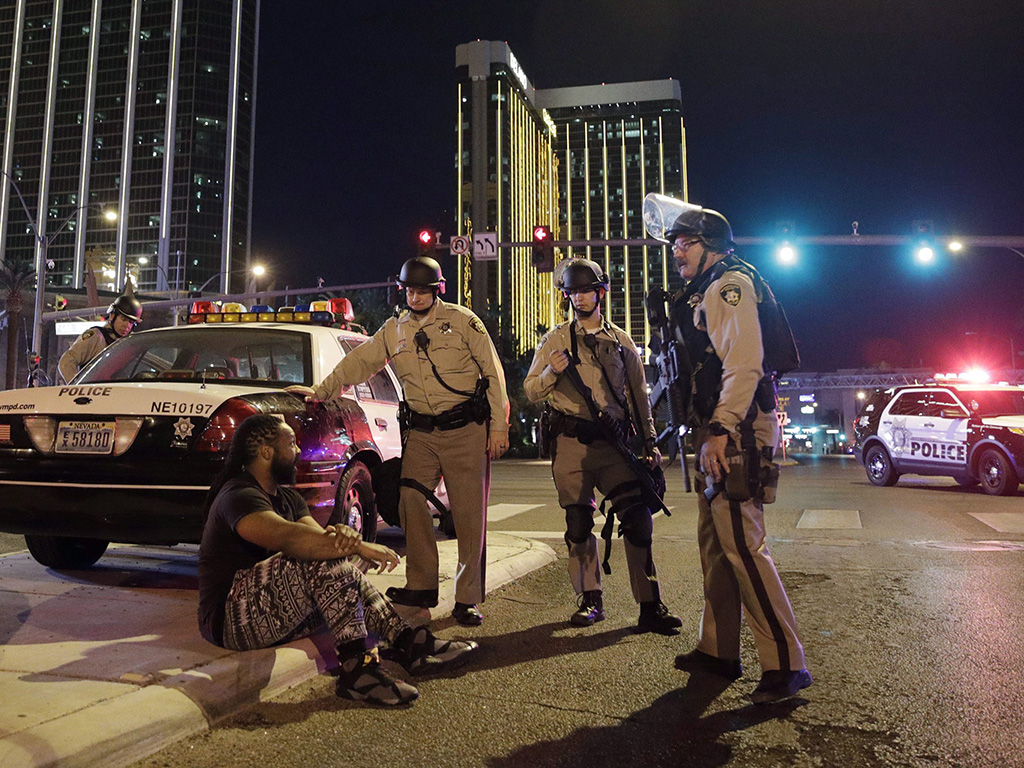 In this Oct. 1, 2017 file photo, police officers stand at the scene of a shooting near the Mandalay Bay resort and casino on the Las Vegas Strip in Las Vegas, Nev.