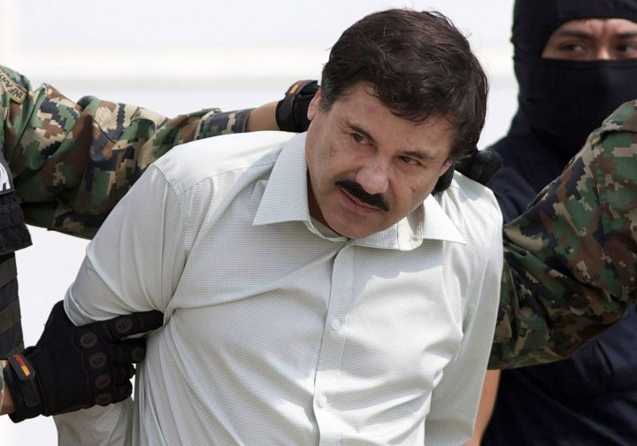 """In this Feb. 22, 2014 file photo, Joaquin """"El Chapo"""" Guzman, the head of Mexico's Sinaloa Cartel, is escorted to a helicopter in Mexico City following his capture in the beach resort town of Mazatlan."""