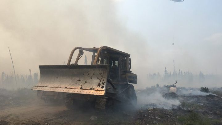 A bulldozer clears debris as crews battle a forest fire near Pikangikum First Nation, Ont. in this undated handout photo. The chief of an Ontario First Nation threatened by a forest fire says a plan to evacuate residents via buses and boats today has been paused because of a lack of space in host communities. THE CANADIAN PRESS/HO, Ontario Ministry of Natural Resources and Forestry.