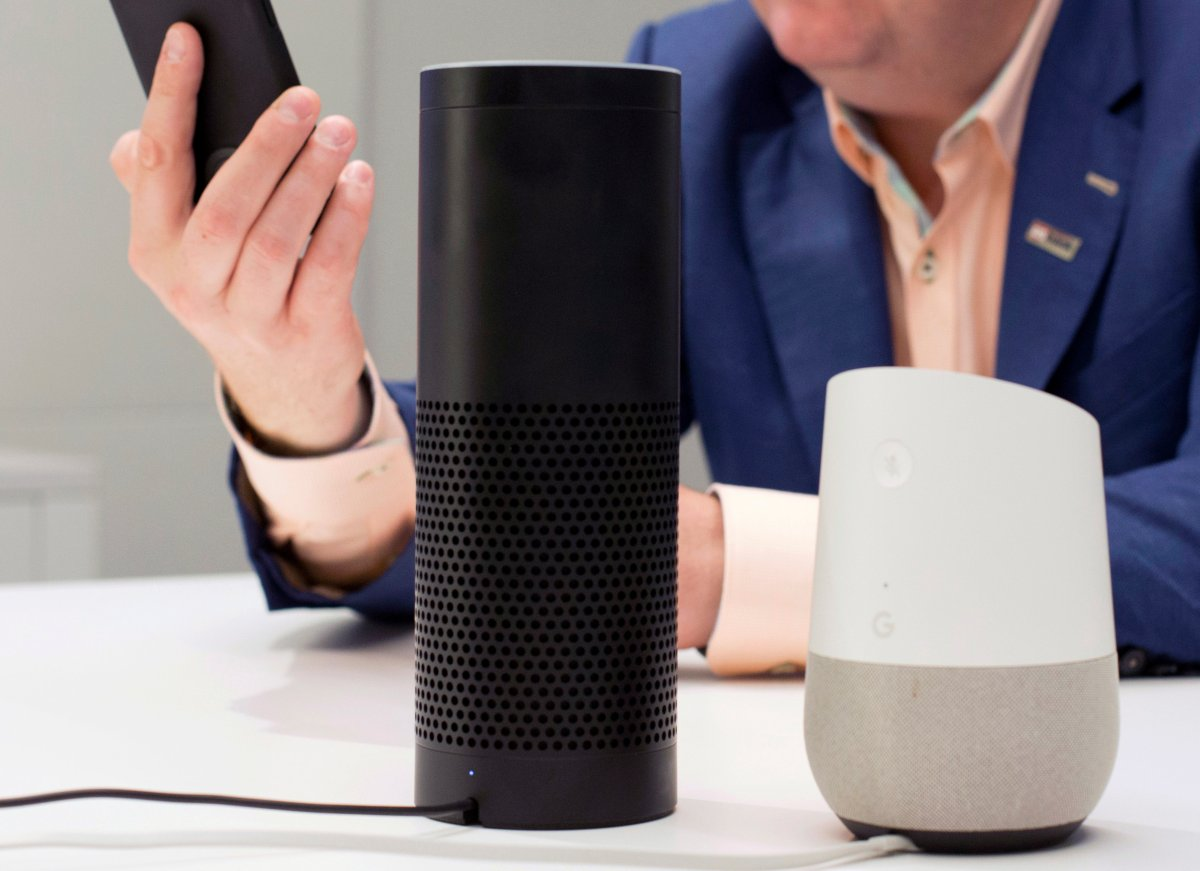 FILE - In this June 14, 2018, photo, an Amazon Echo, center, and a Google Home, right, are displayed in New York.