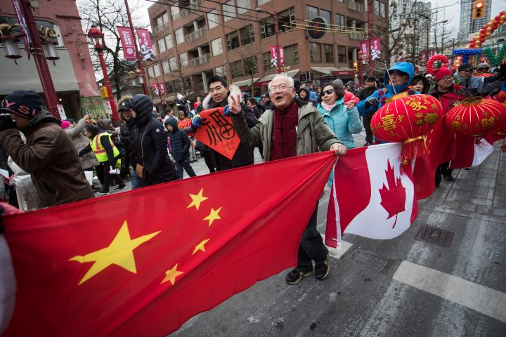 People carry Chinese and Canadian flags while marching in the Chinese New Year Parade in Vancouver.