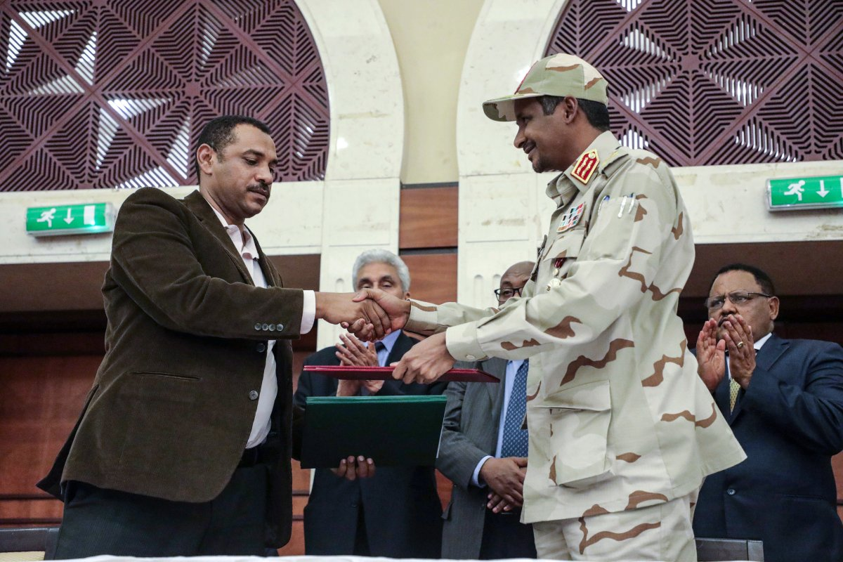 Gen. Mohammed Hamdan Dagalo, right, and Sudan's pro-democracy movement leader Ahmad al-Rabiah shake hands after signing a power sharing document in Khartoum, Sudan, Wednesday, July 17, 2019. The two sides are still at work on a more contentious constitutional agreement that would specify the division of powers.