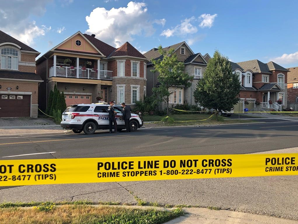 York Regional police officers stand outside of a home in Markham on Sunday, July 28, 2019.