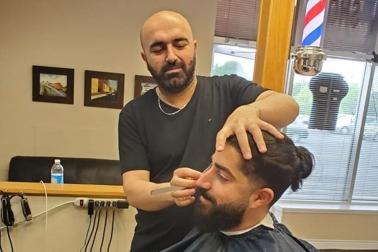 Jakar Al Isso with a customer at Barran Barber Shop.